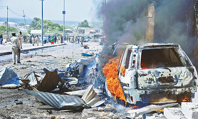 Mogadishu: A car burns following a blast near the heavily fortified gates of the airport in Mogadishu on Wednesday.—AFP