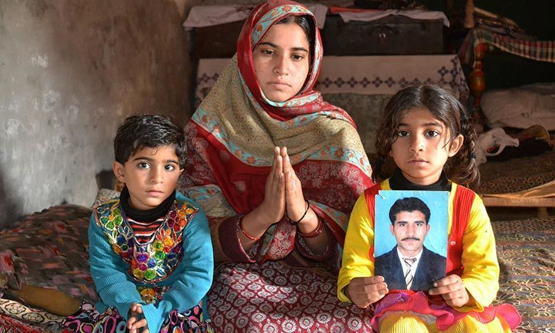 The wife of Mohammad Irfan, who was sentenced to death for drug trafficking in Saudi Ariabia, gestures as she poses for a photograph with her children in Sargodha. — AFP