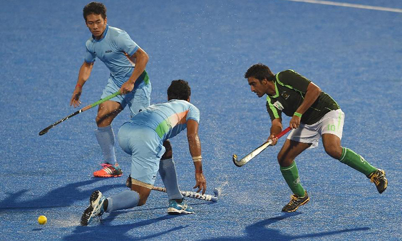 In this photo, Pakistan's Rasool Shafqat (right) makes a pass past India's Kothajit Singh and Gurbaj Singh during the men's hockey final match of the 2014 Asian Games. — AFP/File