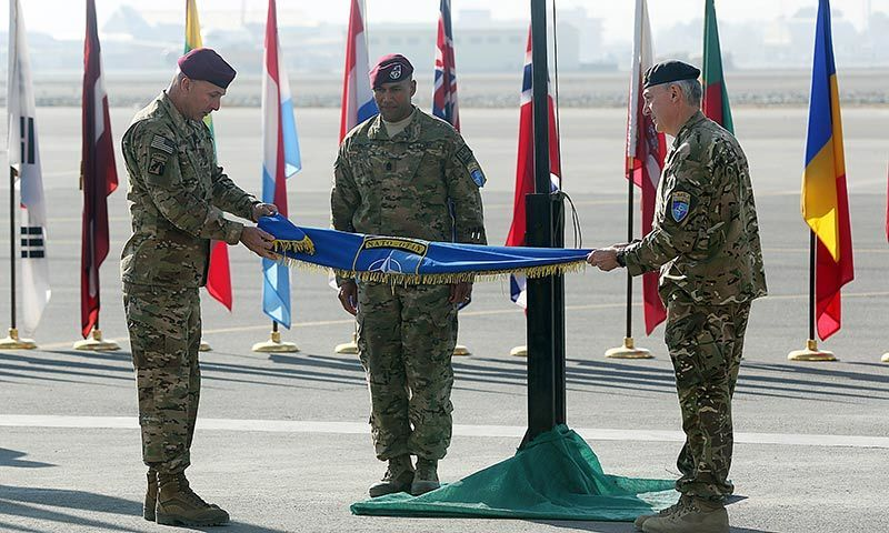 International Security Assistance Force Joint Command (IJC), Lieutenant General Joseph Anderson, left, folds the flag of IJC during a flag-lowering ceremony in Kabul. -AP Photo