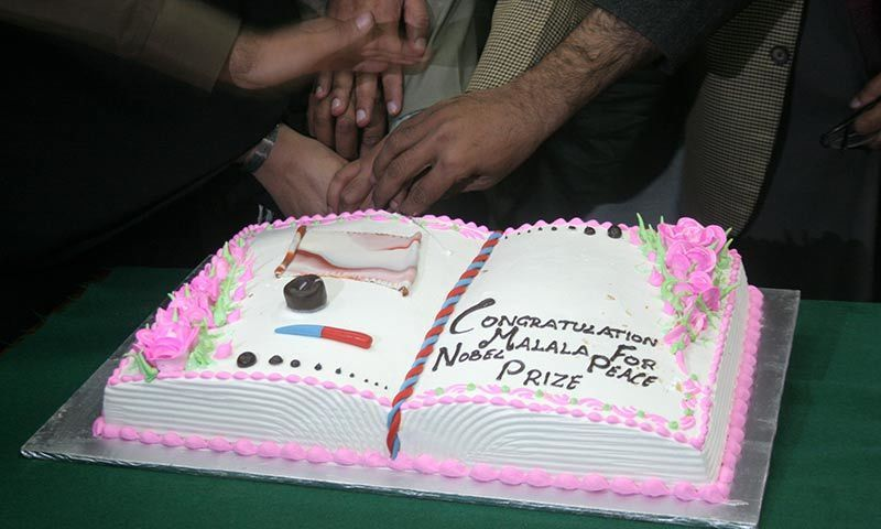 A cake being cut in Peshawar celebrating Malala Yousafzai's Nobel Peace Prize award. -Photo by Zahir Shah Sherazi