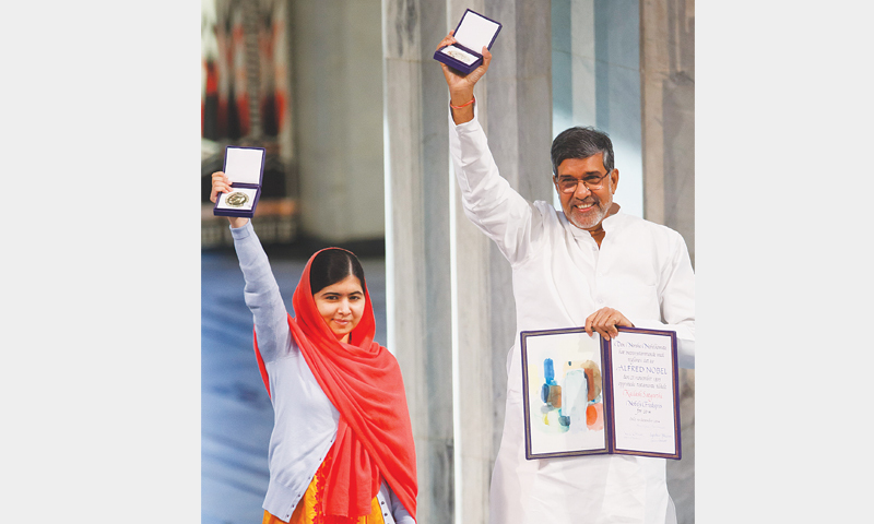 OSLO: Malala Yousufzai and Kailash Satyarthi hold aloft their Nobel Peace Prize medals during the award ceremony here on Wednesday.—AP