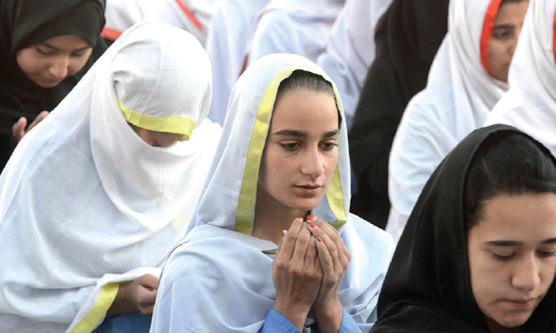 SCHOOLGIRLS pray at a function held in Mingora on Wednesday to celebrate Nobel Peace Prize for Malala Yousafzai. (Right) Members of civil society watch the prize giving ceremony on<br/>television at the Peshawar Press Club. — Photos by Abdul Majeed Goraya and Shahbaz Butt
