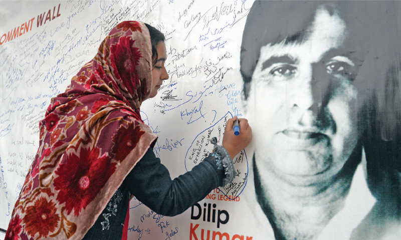 A girl writes her comment on a banner displayed on a wall at Peshawar Press Club on Thursday during signature campaign at the 92nd birthday function of Dilip Kumar. —  White Star