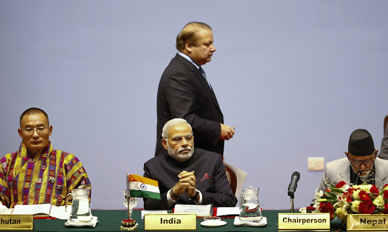 Prime Minister Nawaz Sharif walks past Indian Prime Minister Narendra Modi during the 18th Saarc summit.—Reuters/File