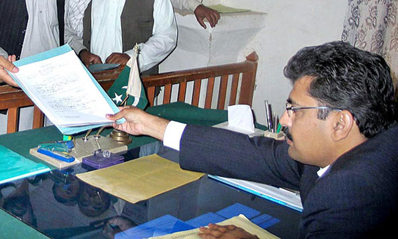 In this photo, a candidate files his nomination papers to the returning officer. — APP/File