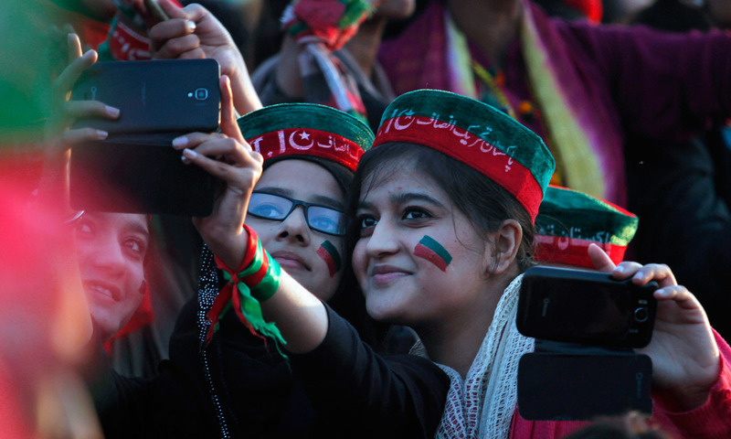 Young supporters take their picture with a mobile phone during a PTI rally in Islamabad. —AP/file