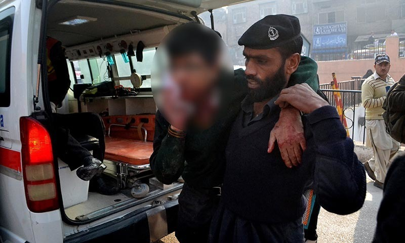 A hospital security guard helps a student injured in the shootout at a school under attack by Taliban gunmen in Peshawar - AP