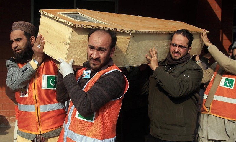 Rescue workers and a family member carry the coffin of a student who was killed during an attack by Taliban gunmen on the Army Public School in Peshawar December 16, 2014. — Reuters