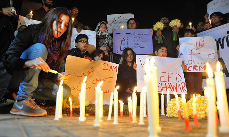 Activist of civil society doing candle vigil for people who died in Peshawar incident. — INP