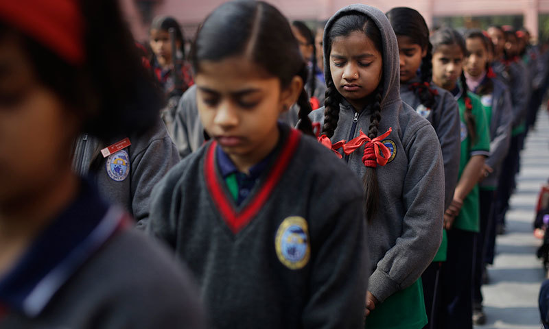 Indian schoolchildren observe a two-minute silence for victims killed in a Taliban attack on a military-run school in Peshawar, in New Delhi, Dec 17, 2014. – AP