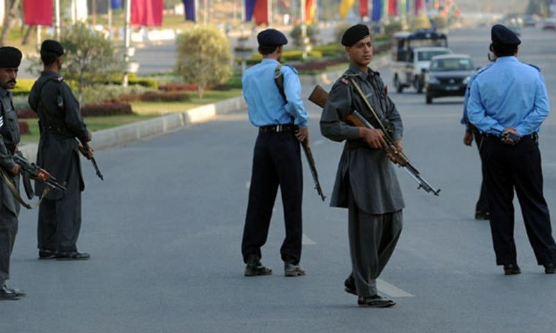 Policemen stand guard on a main road in Islamabad. — AFP/File
