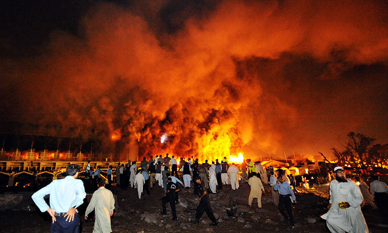 Policemen and onlookers gather as a cloud of smoke billows from the burning Marriott hotel following a powerful bomb blast in Islamabad on September 20, 2008. – AFP/File