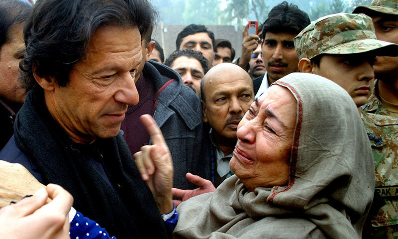 Imran Khan comforts a family member of a student killed in the latest Taliban attack in Peshawar, Dec 22, 23014. — AP