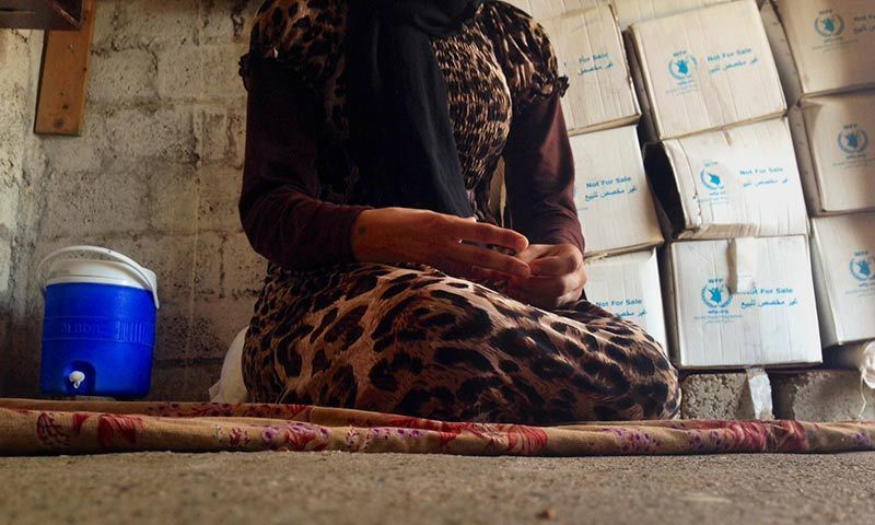 a 15-year-old Yazidi girl captured by the Islamic State group and forcibly married to a militant in Syria sits on the floor of a one-room house she now shares with her family after escaping in early August. — AP