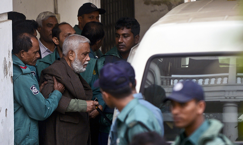 Bangladesh's former Jatiya Party minister Syed Mohammed Kaiser is taken into a van following his verdict at a special court in Dhaka on December 23, 2014. — AFP