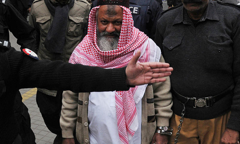 This photograph taken on December 22, 2014 shows police escorting the head of banned Lashkar-i-Jhangvi (LJ) Malik Ishaq as he arrives at the high court in Lahore. - AFP