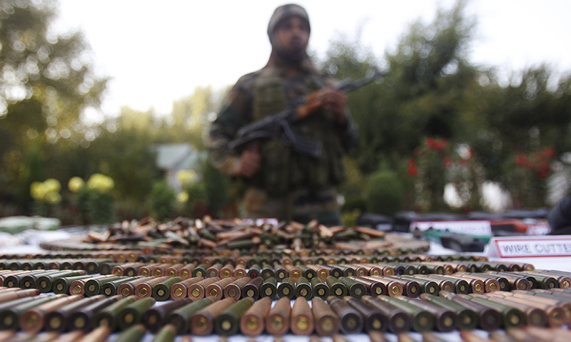This representative image shows a military man stands behind a display of seized arms and ammunition. — Reuters/File