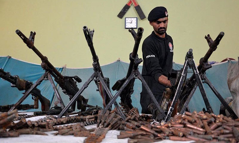 Policeman in Quetta displays weapons recovered during a raid.— INP/File