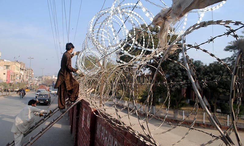 Workers fixing barbwires on the outer wall of Punjab House. — INP