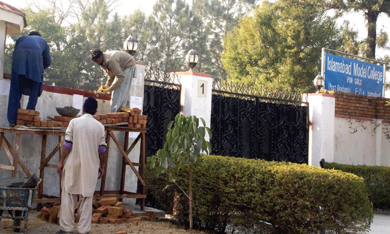 Labourers raising the boundary wall of IMCG, F7/4, on Sunday . — INP