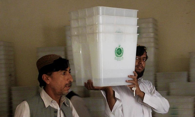 Election commission workers carry ballot boxes.—INP/File