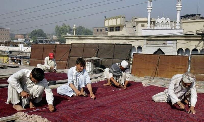 Afghan workers repair a used carpet at a workshop in Peshawar, Pakistan Saturday, Oct. 15, 2011. — AP/file