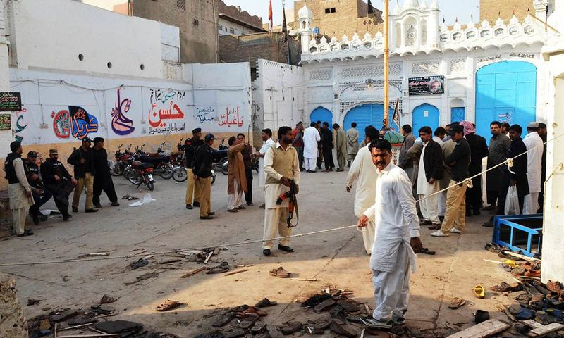 Pakistani security officials gather at the scene following a bomb attack at an imambargah in Shikarpur.— AFP