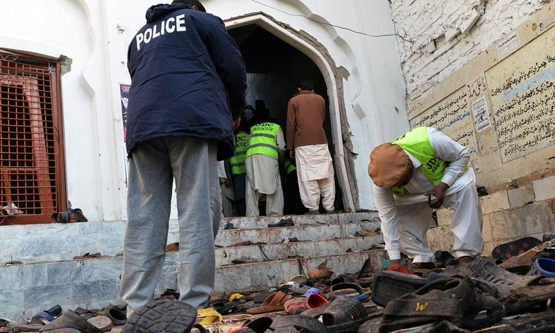 Police and volunteers gather evidence following a bomb attack at an imambargah in Shikarpur. — AFP