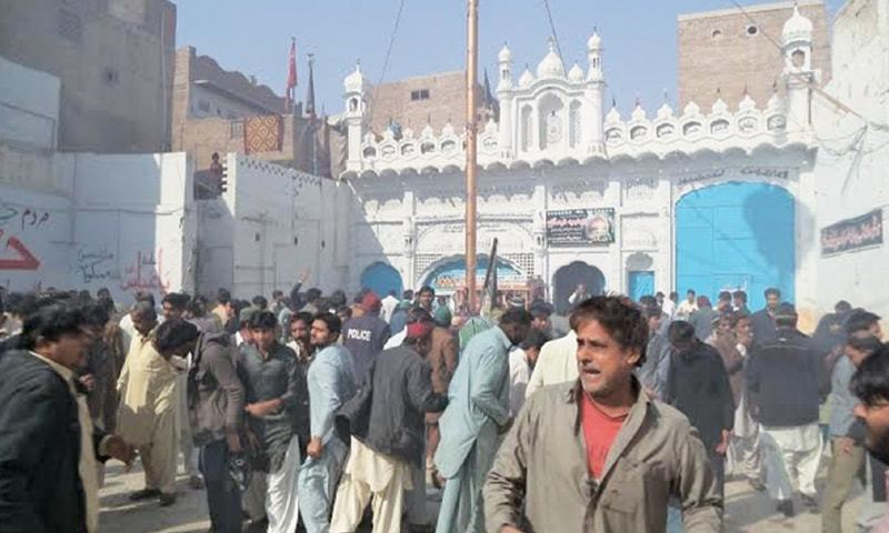 SHIKARPUR: Local people and security personnel gather in front of the Imambargah after the massive blast on Friday.—Dawn