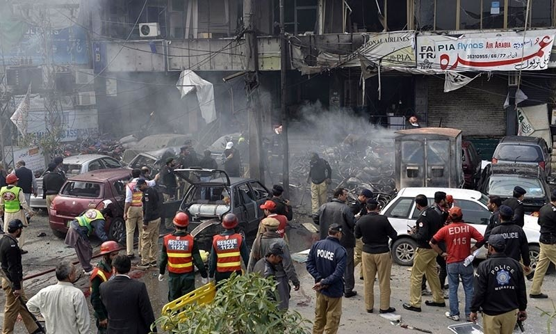Police officials inspect the site after a bomb explosion near the police headquarters in Lahore on February 17, 2015. — AFP
