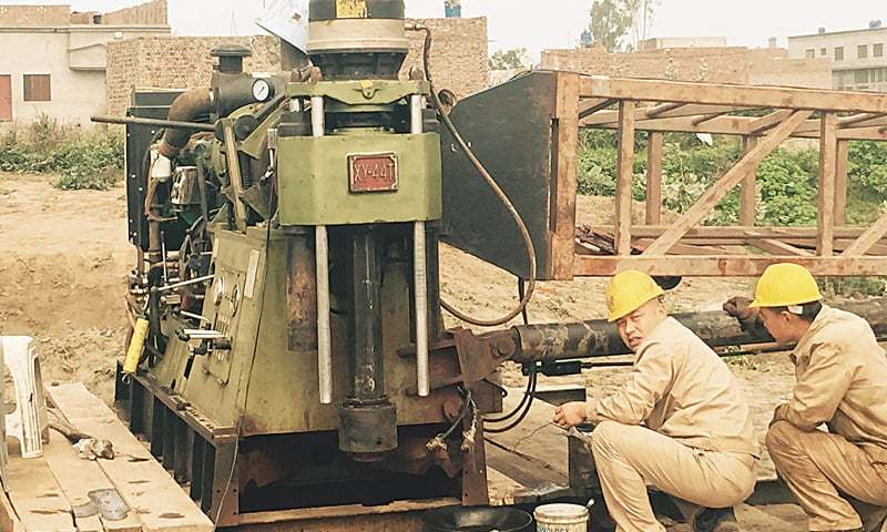 CHINESE workers drilling boreholes in different places in and around Dangraywala village site in Rajoa, some seven kilometres from Chiniot, reportedly to collect samples of gold and copper.—Photo by writer