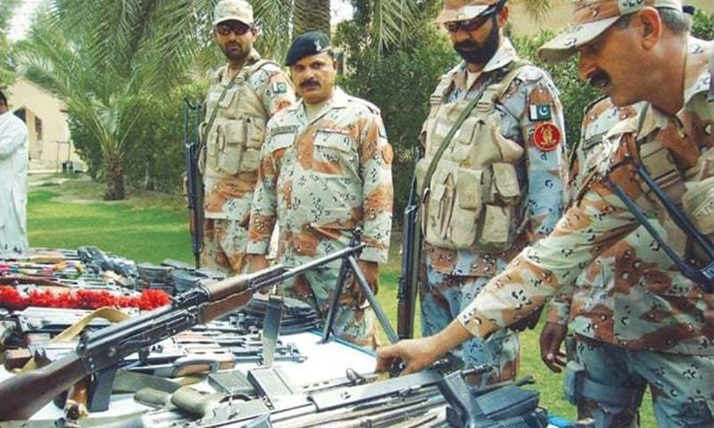 Rangers personnel display seized arms at a media briefing at their headquarters in Sukkur on Friday.—INP