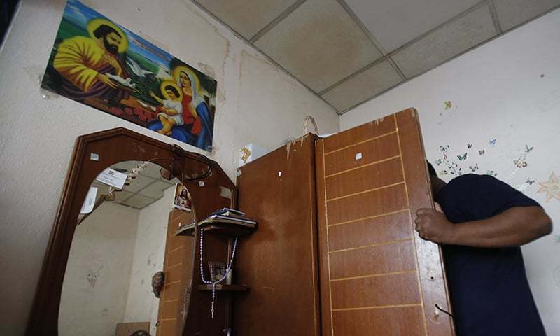 In this Jan. 12, 2015 photo, a Pakistani Christian who fled persecution opens the wardrobe of his room in the outskirts of Bangkok.  — AP