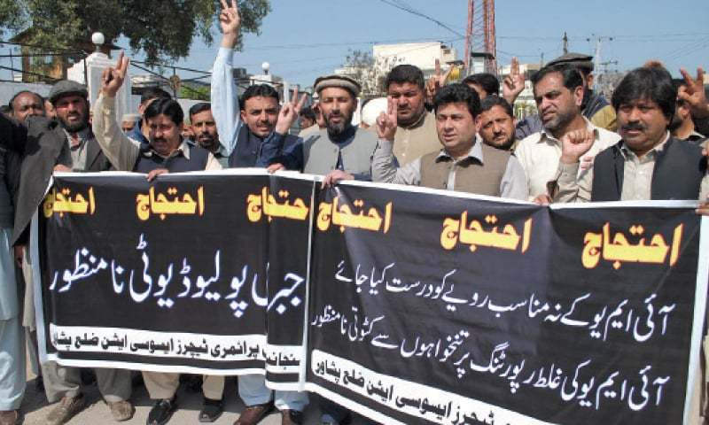 Teachers chant slogans during a protest outside the Peshawar Press Club on Saturday. — INP