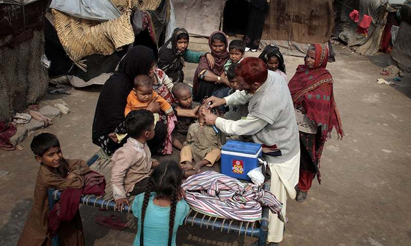 A health worker gives polio vaccines to children in the suburbs of Lahore. AP/File Photo