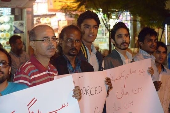 Activists display signs at the demonstration ─ Photo credit: Muzammil Afzal