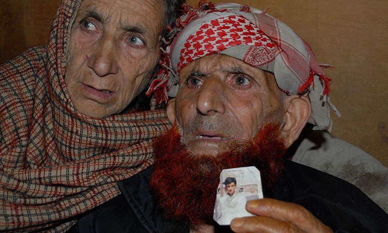 This photograph taken on March 12, 2015 shows the Pakistani Kashmir parents of convicted killer Shafqat Hussain, displaying a photograph of their son, in Muzaffarabad. — AFP