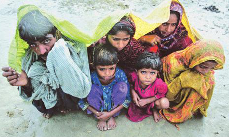Flood victims take shelter from the rains and wind. Photo Courtesy AFP