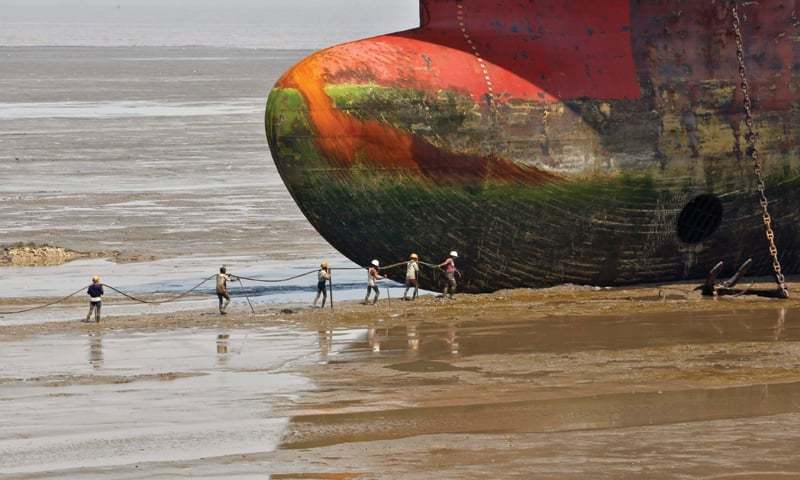 Gujarat: Workers carry a rope line to fasten a decommissioned ship at the Alang shipyard.—Reuters