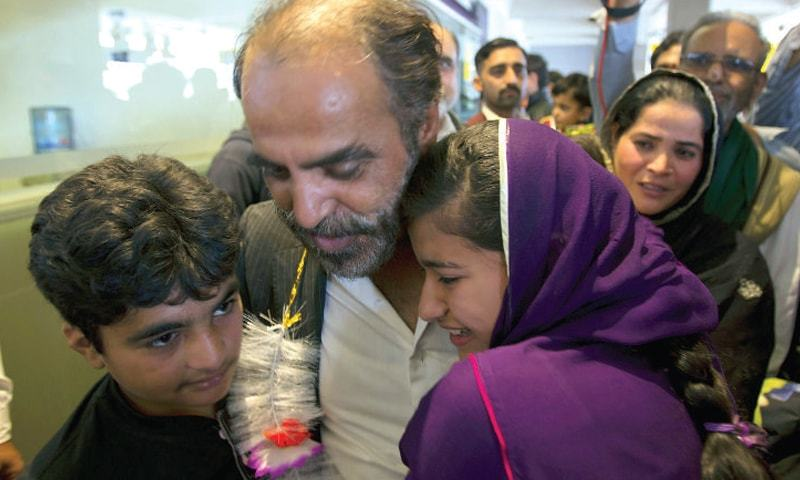 A man, who escaped the fighting in Yemen, hugs his children upon his arrival at Islamabad airport on Friday. — Photo by Tanveer Shahzad