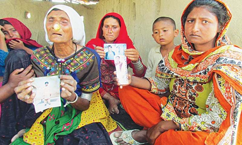 SADIQABAD: Women show pictures of their relatives who were shot dead in Turbat.—Online