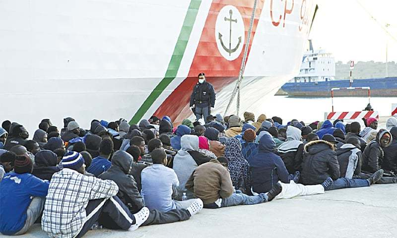 Migrants rest after disembarking at the Sicilian harbour of Augusta on Thursday.—Rueters