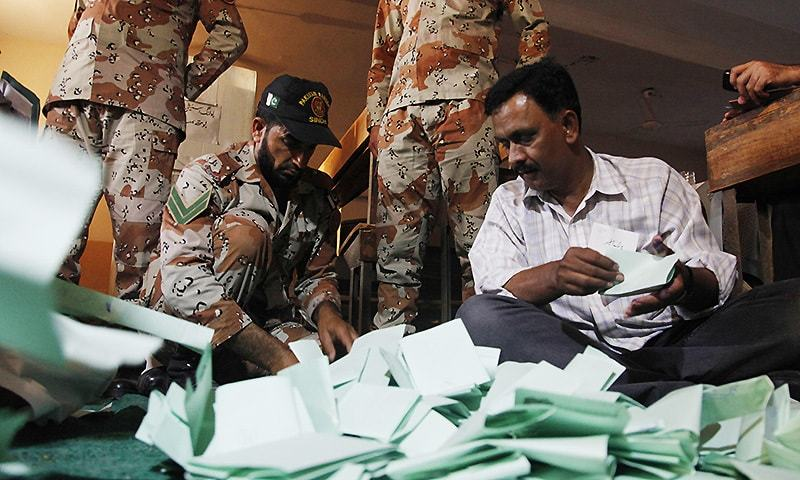 A soldier of the para-military force helps volunteers to count ballots for by-elections held in Karachi, Pakistan, Thursday, April 23, 2015. — AP