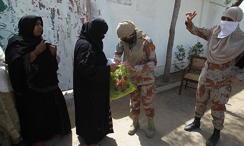 Female personnel of the para-military force check voters as they enter to cast their votes for by-elections held in Karachi, Pakistan, Thursday, April 23, 2015.— AP