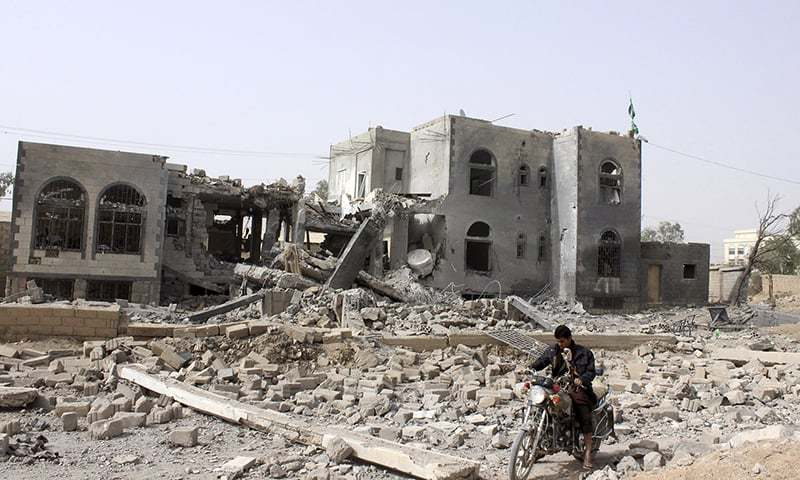 A man rides a motorcycle past a headquarters of the Houthi group, which was destroyed after an air strike by a Saudi-led coalition, in Saada. ─ Reuters