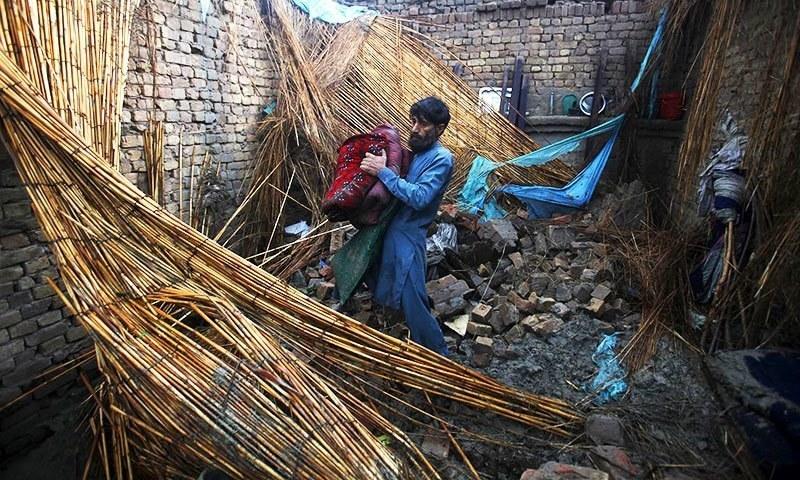 پشاور کے نواحی علاقے میں ایک شخص شدید بارشوں سے تباہ ہونے والے اپنے گھر میں سے سامان اکٹھا کر رہا ہے۔ — رائٹرز