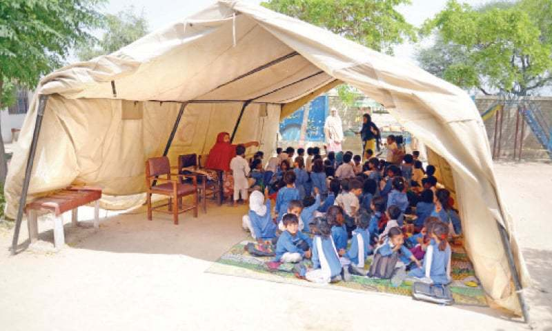 Students attend their class in a tent  at Islamabad Model School for Girls, H-13. The other picture shows students sitting in the open. — Photos by Khurram Amin
