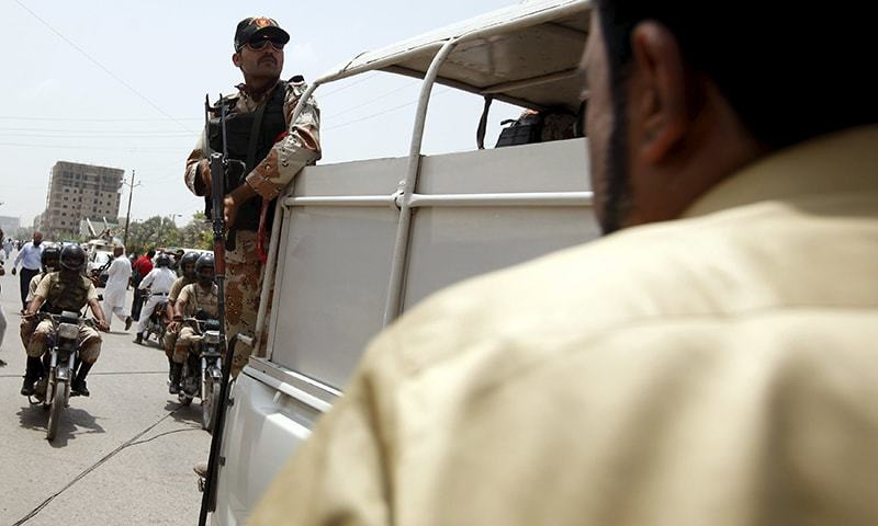 A paramilitary solder stands guard on a van outside a hospital after an attack on a bus in Karachi, Pakistan, May 13, 2015. — Reuters