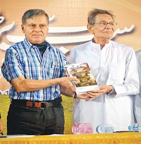 The author presents his book to Mairaj Mohammad Khan at the launch on Saturday evening.—White Star